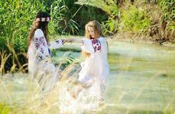 Duas meninas na roupa nacional ucraniana que nadam no rive Imagens de Stock
