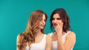 Duas meninas nas camisas brancas estão abraçando o riso em um fundo verde filme