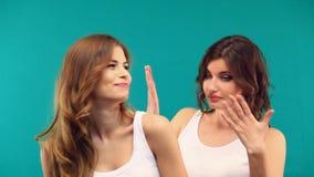 Duas meninas nas camisas brancas estão abraçando o riso em um fundo verde video estoque