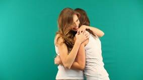 Duas meninas nas camisas brancas estão abraçando o riso em um fundo verde vídeos de arquivo