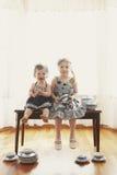 Duas meninas no banco com pratos imagens de stock