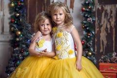 Duas meninas no branco elegante com vestidos amarelos Foto de Stock Royalty Free