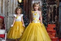Duas meninas no branco elegante com vestidos amarelos Fotos de Stock Royalty Free