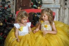Duas meninas no branco elegante com vestidos amarelos Fotos de Stock