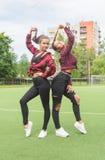 Duas meninas no campo de jogos da escola, chapinham Fotos de Stock