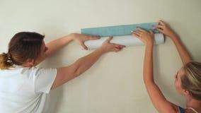 Duas meninas no canteiro de obras colam o papel de parede à parede filme