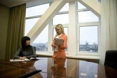 Duas meninas no escritório, saliência e secretária Imagens de Stock