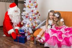 Duas meninas não esperaram Santa Claus e não foram dormir, Papai Noel em presentes postos este tempo sob a árvore de Natal Imagem de Stock Royalty Free