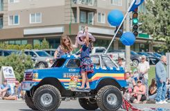 Duas meninas no flutuador diminuto da parada do jipe acenam às multidões na parada do debandada foto de stock royalty free