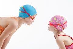 Duas meninas no olhar dos ternos de natação em se Imagem de Stock