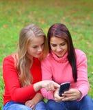 Duas meninas no parque com um telefone celular no outono Fotografia de Stock Royalty Free