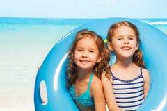 Duas meninas no roupa de banho com anel de borracha azul grande Imagem de Stock