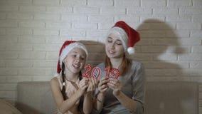 Duas meninas nos chapéus de Santa estão guardando os números vermelhos 2019, sentando-se junto no sofá, na dança e no sorriso vídeos de arquivo