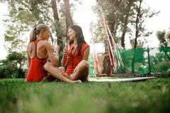 Duas meninas nos roupas de banho vermelhos que sentam-se e para beber o champanhe fotografia de stock royalty free