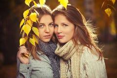 Duas meninas novas da forma na camisa e no lenço brancos no outono estacionam Fotografia de Stock Royalty Free