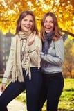 Duas meninas novas da forma na camisa e no lenço brancos que andam na cidade Imagens de Stock Royalty Free