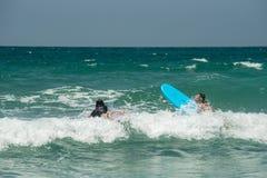Duas meninas novas do surfista que montam as ondas imagem de stock
