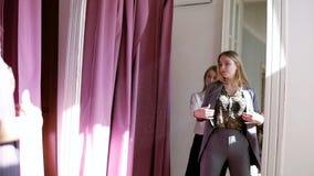 Duas meninas ou irmãs que compram junto: a fêmea loura nova atrativa está tentando um terno cinzento novo perto da encaixe-sala o filme
