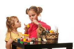 Duas meninas para pintar ovos da páscoa em um fundo branco Fotos de Stock Royalty Free
