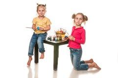 Duas meninas para pintar ovos da páscoa em um fundo branco Foto de Stock Royalty Free
