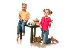 Duas meninas para pintar ovos da páscoa em um fundo branco Imagem de Stock
