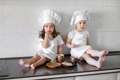 Duas meninas pequenas do padeiro estão bebendo o chá com pabcakes na cozinha fotografia de stock