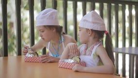 Duas meninas pequenas sob a forma dos cozinheiros sentam-se na tabela e comem-se as batatas quentes cozinhadas por elas vídeos de arquivo