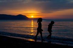 Duas meninas que andam ao longo da praia durante o por do sol fotografia de stock royalty free