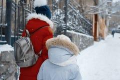 Duas meninas que andam ao longo da rua nevado do inverno da cidade, crianças estão guardando as mãos, para trás vista foto de stock royalty free