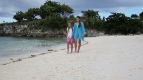 Duas meninas que andam em uma praia tropical video estoque