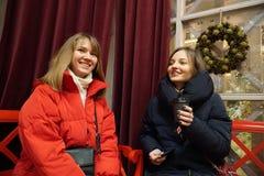 Duas meninas que apreciam a época de férias, a conversa e o sorriso do inverno imagens de stock royalty free