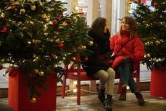 Duas meninas que apreciam luzes de Natal da época de férias e da conversa do inverno no fundo, crepúsculo Perto da árvore de Nata imagem de stock royalty free