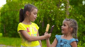 Duas meninas que comem o gelado do picolé no parque vídeos de arquivo