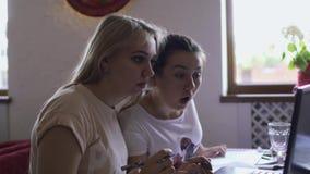 Duas meninas que comunicam-se um com o otro usando o portátil no café video estoque