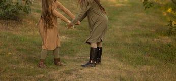 Duas meninas que correm ao redor, girando na grama no parque, nas madeiras Mãos de escalada, uma caminhada imagem de stock