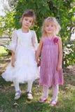 Duas meninas que desgastam os vestidos bonitos que prendem as mãos Imagem de Stock Royalty Free