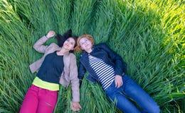 Duas meninas que encontram-se na grama no verão Fotos de Stock