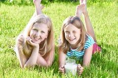 Duas meninas que encontram-se no prado ensolarado com o jarro de leite foto de stock