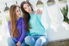 Duas meninas que escutam a música em seus smartphones Foto de Stock