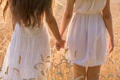 Duas meninas que estão junto no campo de trigo, close up foto de stock royalty free