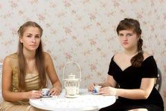Duas meninas que falam em uma tabela em um café Imagens de Stock Royalty Free