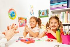 Duas meninas que fazem exercícios do dedo como seu professor Imagens de Stock