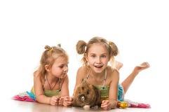 Duas meninas que jogam com coelhinho da Páscoa em um fundo branco Foto de Stock Royalty Free