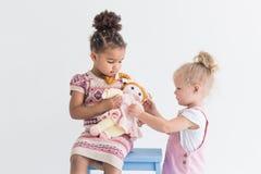 Duas meninas que jogam em um fundo branco imagens de stock