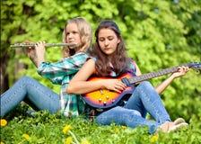 Duas meninas que jogam a guitarra e a flauta no parque Foto de Stock Royalty Free