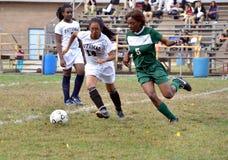 Duas meninas que jogam um jogo de futebol da High School das meninas fotos de stock
