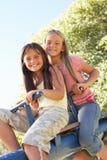 Duas meninas que montam no balanço no campo de jogos fotos de stock royalty free