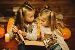 Duas meninas que preparam-se para o feriado Noite, velas, abóbora, contos imagem de stock