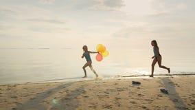 Duas meninas que riem junto Jogando na praia, alcançando um com o otro vídeos de arquivo