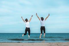 Duas meninas que saltam na praia imagens de stock royalty free